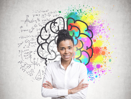 Smiling confident young African American woman wearing a white shirt and black pants standing with crossed arms and looking at the viewer. A concrete wall with a colorful brain sketch and formula