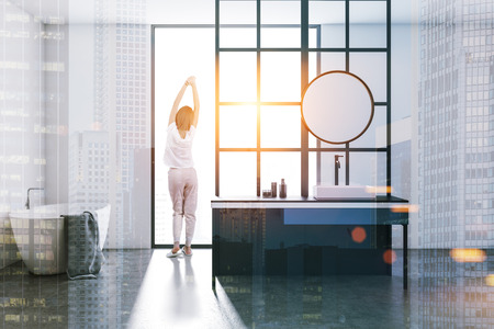 Interior of a modern bathroom with loft window, a concrete floor, a sink with a round mirror and a white bathtub. A woman. 3d rendering mock up toned image double exposure