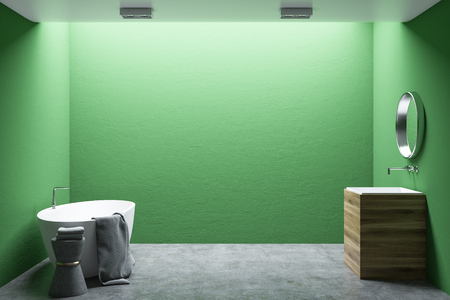 Minimalist bathroom interior with green walls, a concrete floor, a white tub and a wooden sink. A round mirror. 3d rendering mock up