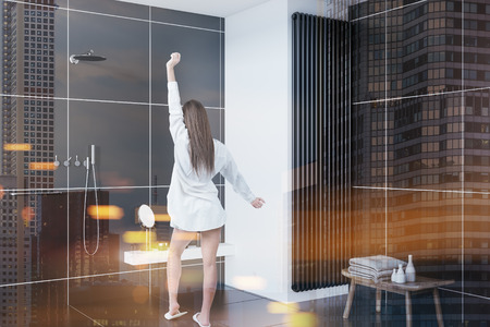 Rear view of a woman standing in a bathroom corner with black tiles and a loft window. 3d rendering toned image double exposure