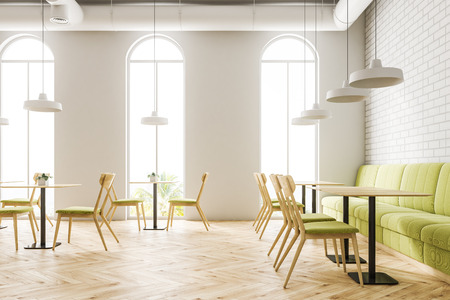 Industrial style cafe interior with white brick walls, a wooden floor, arched windows and wooden tables with chairs and green couches. 3d rendering mock up