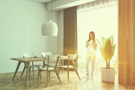 Woman with a smartphone in a white and wooden dining room corner with a wooden floor, a wooden table with chairs and a loft window. 3d rendering mock up toned image double exposure