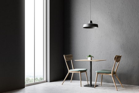 Wooden chairs and table standing in a gray wall room with a concrete floor and a lamp hanging above the table. An arched window. 3d rendering mock up