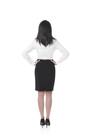 Rear view of a young businesswoman with long black hair standing with her hands on the waist and looking forward. An isolated full length portrait 版權商用圖片