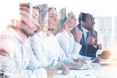 Members of a diverse business team sitting together at a table looking forward. A cityscape background. Concept of HR success and job interview. Toned image double exposure mock up.
