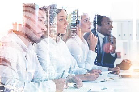 Miembros de un equipo empresarial diverso sentados juntos en una mesa mirando hacia adelante. Un fondo de paisaje urbano. Concepto de éxito de recursos humanos y entrevista de trabajo. Maqueta de doble exposición de imagen tonificada. Foto de archivo