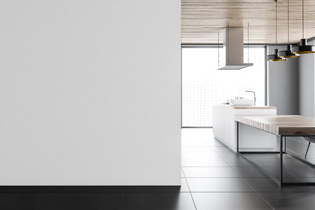 Panoramic kitchen interior with white walls, a tiled floor and a long wooden table with chairs. A blank wall to the left. 3d rendering mock up Reklamní fotografie