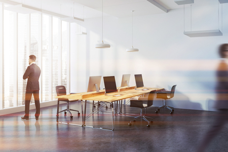 Corner of a modern consulting company office with panoramic windows with a city view and wooden computer desks standing in row. Businessman looking in window. 3d rendering mock up toned image blurred Reklamní fotografie