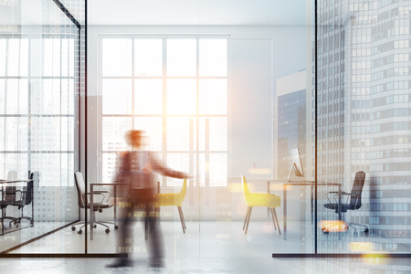Young businessman entering a luxury office with white and glass walls, loft windows and rows of computer tables. 3d rendering mock up toned image blurred