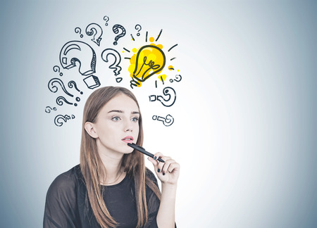 Pensive young woman with long fair hair holding a pen near her chin. Question marks and a light bulb drawn on a gray wall behind her. Mock up Stock Photo