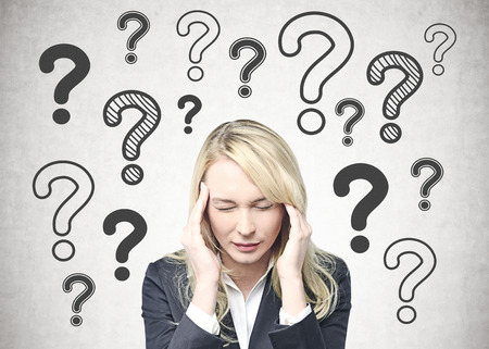 Young caucasian businesswoman with long blond hair wearing a suit having a severe headache. A concrete wall background with question marks Stock Photo