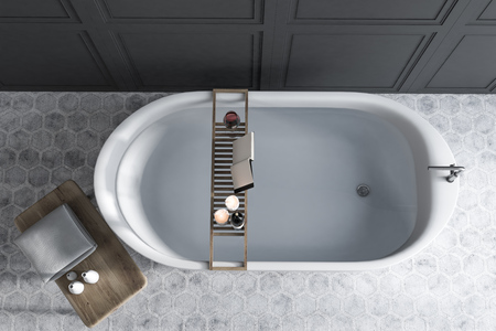Elegant white bathtub filled with water standing in a luxury bathroom interior with gray walls, and a hexagon tile floor. A mock up open book on a shelf. 3d rendering top view