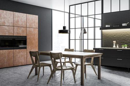 Black and concrete wall kitchen and dining room corner with a tiled floor, brown closets with built in appliances, black countertops and a wooden table with chairs. 3d rendering mock up