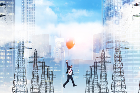 Businessman flying holding a red balloon over a row of high voltage steel power line supports. Blue sky with many clouds and cityscape. 3d rendering mock up Banque d'images - 106635173