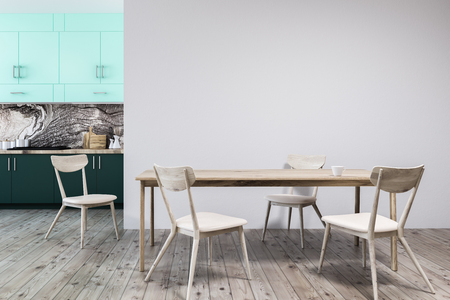 White and marble wall kitchen interior with a wooden floor, green closets and countertops, and a blank white wall to the right. A table with chairs. 3d rendering mock up Stock Photo