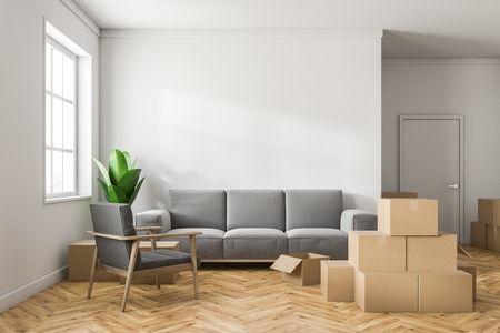 Empty white room interior with white walls, a wooden floor, a large window and stacks of closed cardboard boxes. A gray sofa. Concept of moving in. 3d rendering mock up