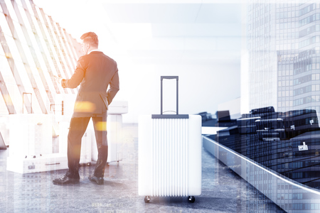 Businessman looking at his smartphone standing in an airport near a large white suitcase and a conveyor belt with luggage. Business trip concept. 3d rendering mock up toned image double exposure city Stock Photo