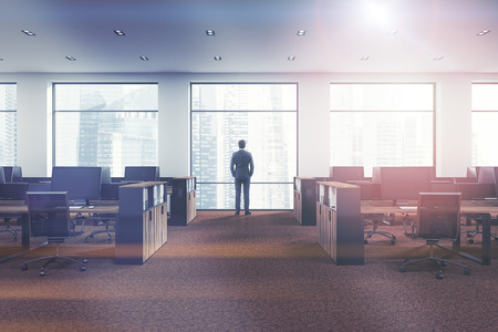 Businessman looking at city in open space office of a modern company with white walls, panoramic windows, brown carpet and rows of wooden computer tables. 3d rendering mock up toned image Stock Photo
