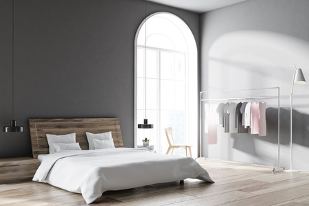 Scandinavian style bedroom with grey walls, a wooden floor, a clothes rack, and a master bed with bedside tables. Arched windows. 3d rendering mock up Stock Photo