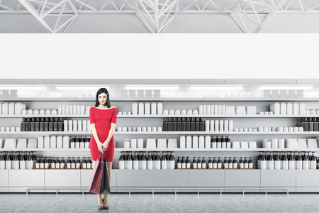 Attractive young woman wearing a red dress and holding paper bags standing over row of store shelves with mock up bottles and boxes. Concept of marketing and consumption. 3d rendering mock up