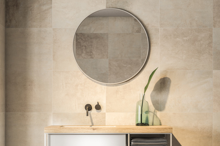 Bathroom sink with a round mirror hanging on a beige tiled wall. Concept of interior design. 3d rendering