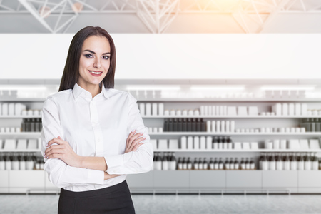 Confident young manageress smiling and standing with crossed arms over row of store shelves with mock up bottles and boxes. Concept of marketing, consumption and product placement 3d rendering mock up