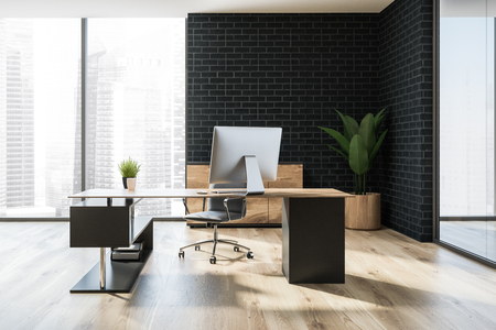 Modern manager office interior with a wooden floor, black brick walls, a stylish computer table and a panoramic window. 3d rendering Stock Photo