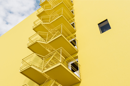 Modern building exterior with yellow walls, white doors and emergency exit stairs. Low angle view Concept of plan b and creative thinking. 3d rendering mock up