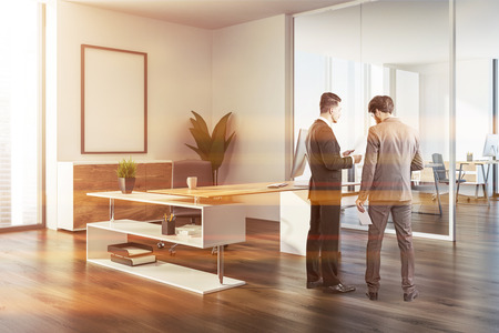 Two businessmen talking in modern manager office corner with a wooden floor, white walls, a stylish computer table and a mock up poster frame. 3d rendering toned image