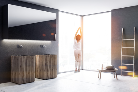 Woman in pajamas near wooden double sink with a long horizontal mirror hanging above it in a luxury black wall loft bathroom interior. Spa Hotel. Ladder and table. 3d rendering mock up toned image