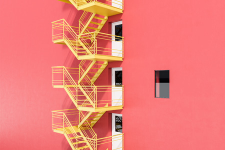 Modern building exterior with red walls, white doors and yellow emergency exit stairs. Concept of plan b and creative thinking. 3d rendering mock up