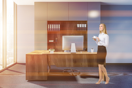 Blonde businesswoman in modern manager office interior with a carpet on floor, blue walls, a stylish computer table and a bookcase. Side view. 3d rendering mock up toned image Stock Photo