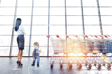 Businesswoman and cute little boy in jeans overalls near supermarket carts row next to a panoramic window. Marketing and consumerism concept. 3d rendering copy space toned image double exposure Stock Photo