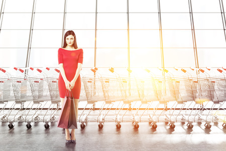 Beautiful caucasian woman in red dress holding paper bags standing near supermarket carts row and panoramic window. Marketing, shopaholism and consumerism concept. 3d rendering copy space toned image