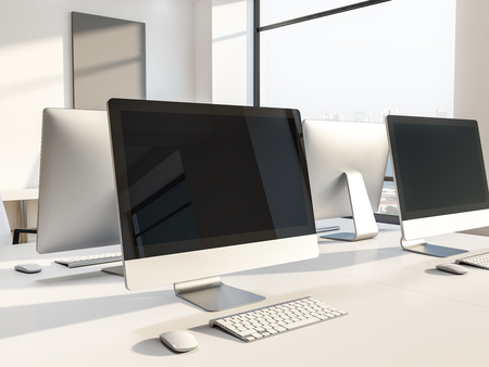 Black computer screens on white office or computer lab tables with gray mock up pictures in the background. 3d rendering Stock Photo