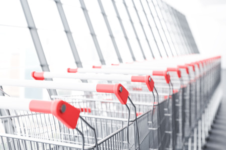 Perspective view of a long supermarket carts row standing along a panoramic window. Concept of marketing and consumerism. 3d rendering copy space