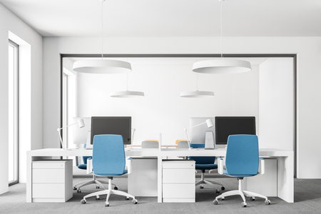 Open space office with white walls, carpet on the floor, loft windows and rows of computer tables with blue chairs. 3d rendering mock up Stock Photo