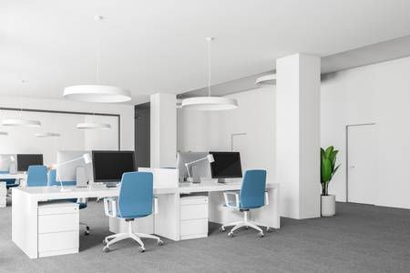 Open space office corner with white walls, carpet on the floor, loft windows and rows of computer tables with blue chairs. 3d rendering mock up Stock Photo