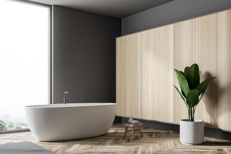 Stylish gray bathroom fragment with wooden floor, gray rug, window with tropical view, wooden wall, big bathtub, and a potted plant. 3d rendering copy space