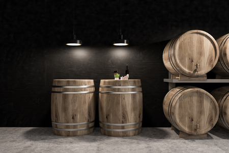 Wine cellar interior with black walls, a grey honeycomb pattern floor and rows of wooden kegs. Wine bottle and glass on one of the kegs. 3d rendering