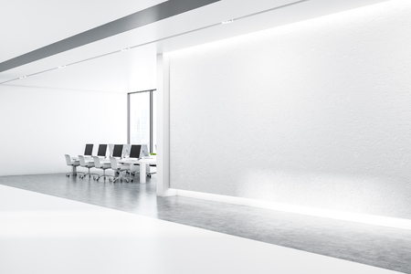 Minimalistic office interior with white walls, concrete floor with rows of massive white tables with black computer screens and panoramic windows. Side view of mock up wall. 3d rendering Stock Photo
