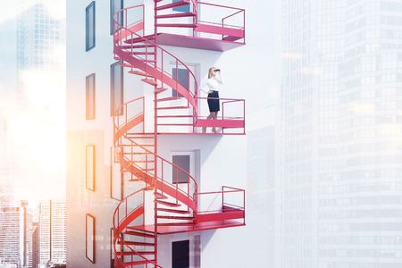 Blonde businesswoman with binoculars standing on spiral red emergency exit staircase of white building. Cityscape background. 3d rendering toned image double exposure