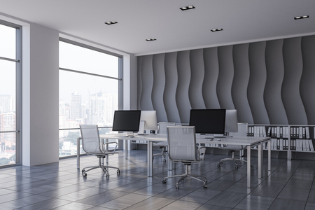 Corner of open plan office with wave pattern wall, wooden tiles floor, rows of computer tables with metallic chairs and shelves with folders in them. 3d rendering Stock Photo