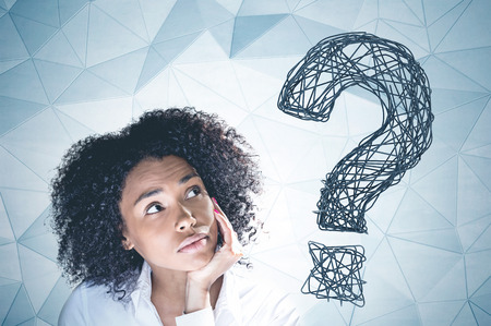 Portrait of thoughtful young african american woman with curly black hair looking up with her hand on the chin. Gray wall background with big question mark on it.