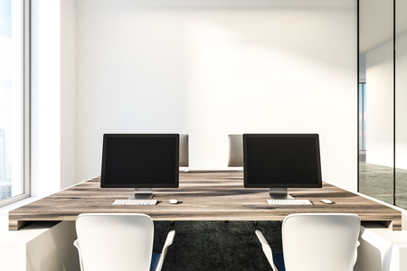 Black computer screens standing on wooden tables in minimalistic white office with concrete floor and loft windows. 3d rendering copy space