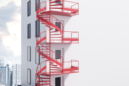 Corner of white building with spiral red emergency exit staircase. Cityscape background. 3d rendering mock up