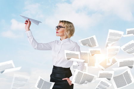 Calm young businesswoman in glasses launching paper plane. Documents flying around. Sky with clouds background. Staying calm during crisis and effective management concept. Double exposure