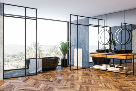 Modern bathroom corner with gray and glass walls, wooden floor, black bathtub and black double sink with round mirrors hanging above it. 3d rendering