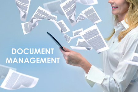 Side view of unrecognizable blonde businesswoman looking at her tablet computer standing in document storm with document management text.