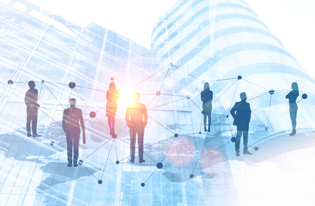 Silhouettes of business people standing on world map over cityscape background. Global work market and trade concept. Toned image double exposure